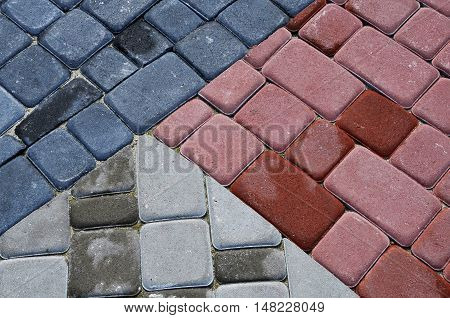 dark grey and red paving slabs laid out on different size cubes