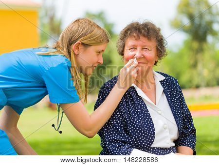 Doctor nursing old woman with nose drop because of ragweed allergy and flu.