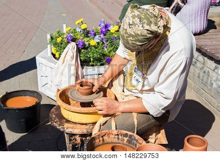 Zaporizhia/Ukraine- September  17, 2016: Family festival of homemade pickled canned vegetables and preserves. Outdoors pottery workshop.  Potter presenting  process of ceramic jug creation on a turning wheel.