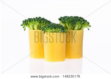 A group of three green broccoli embedded into pasta on a white backround