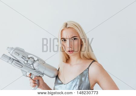 Close up portrait of a beautiful pensive blonde girl in silver shiny dress holding blaster isolated on the grey background
