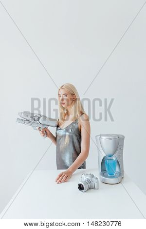 Beautiful young fashion blonde woman holding blaster while standing at the table isolated on the grey background