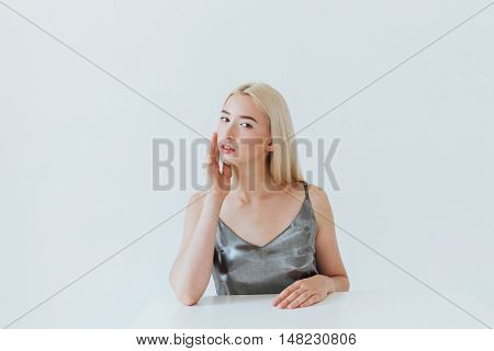 Beauty portrait of a young blonde pensive girl sitting at the white table isolated on the grey background