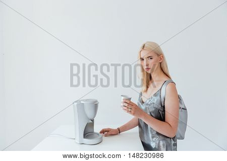 Young beautiful pensive girl wearing backpack and silver dress holding cup while standing at the table isolated on the grey background