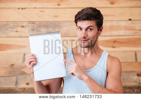 Happy casual man pointing finger at blank notebook isolated on a wooden background