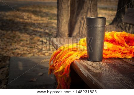 Hot tea in a thermos in autumn park.