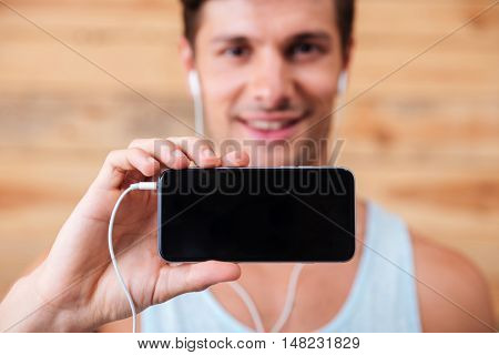 Happy young man in earphones showing blank screen cell phone over wooden background