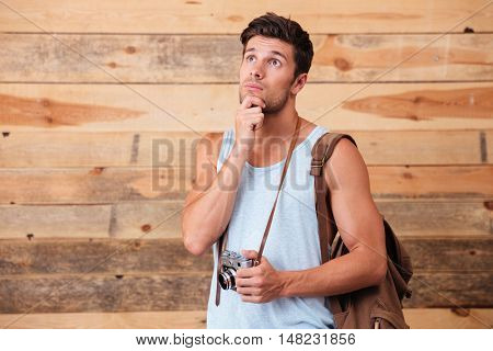 Portrait of a pensive photographer with backpack holding camera isolated on a wooden background