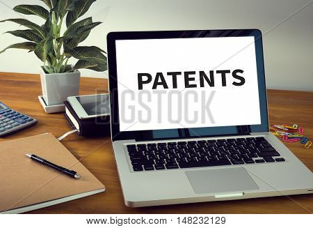 PATENTS Laptop on table. Warm tone businessman working
