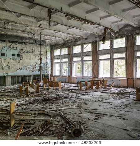 ruined assembly hall with debris and overturned chairs in abandoned Pripyat school