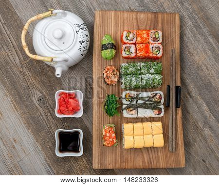 set of different rolls and sushi with soy and nori in bowls and kettle on wooden table, top view