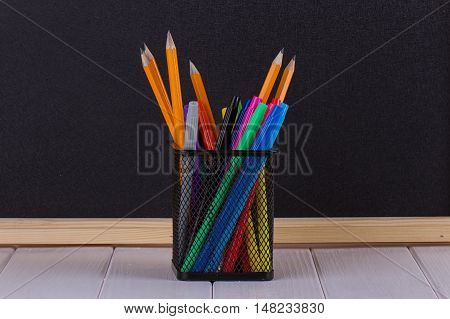 Pencils in the stand in front of a black school Board. Concept of education or back to school on green background