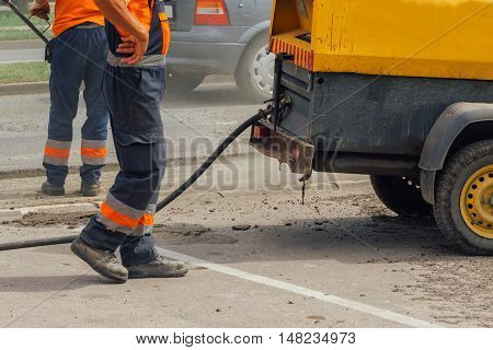 Unidentifiable road maintenance workers repairing driveway road construction works
