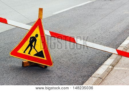 Road construction work sign on asphalt driveway