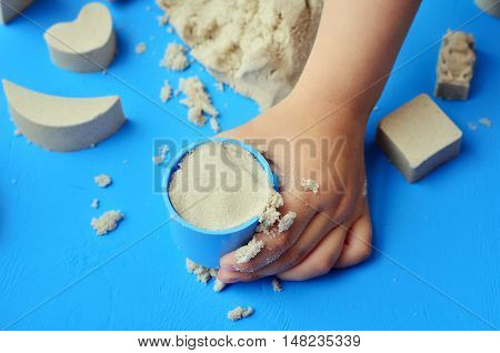 Child playing with kinetic sand. The kids fills figures on a bright background