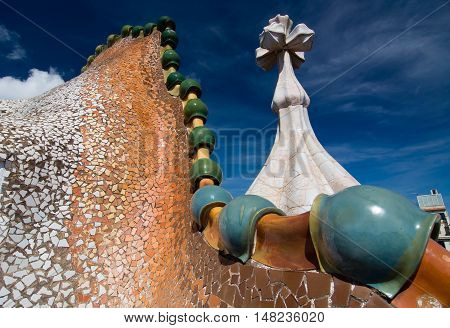 BARCELONA - SEPTEMBER 20, 2014: Rooftop of the house Casa Batllo designed by Antoni Gaudi. Ceramic tiles with tower and bulb. Dragon's spine roof arch. Barcelona, Spain.