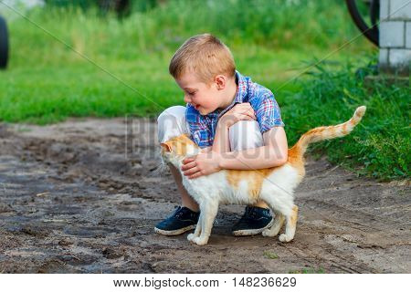 smiling little boy affectionately embraces a red cat. outdoor