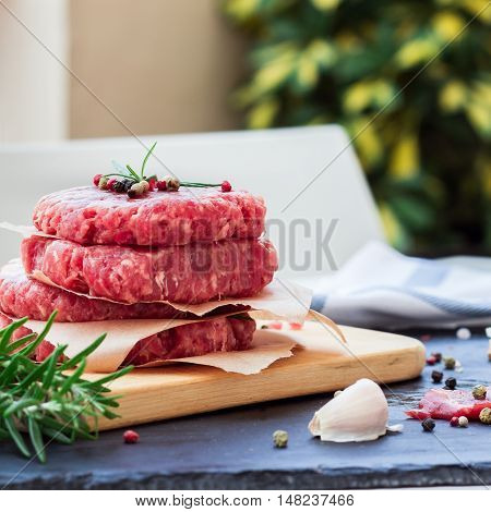 Fresh raw burger cutlets from the farmers market on a black grunge table. Selective focus, outdoor background