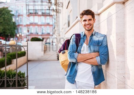Portrait of a smiling casual man with backpack and arms folded standing on the street