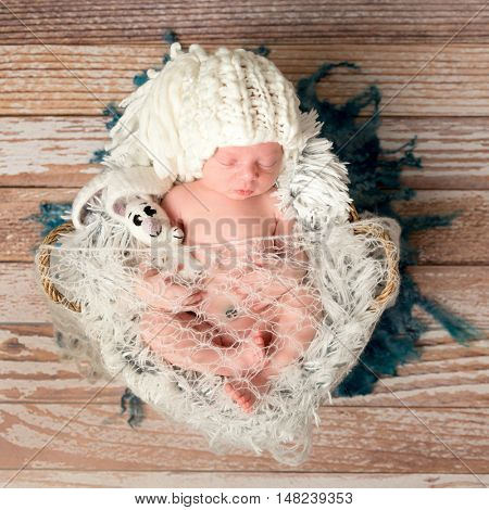 tiny newborn baby in white knitted hat lying on fur, top view