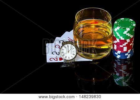 Cards with colorful chips to poker and tumbler of whiskey with the watch