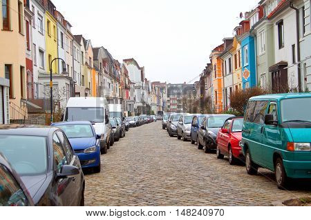 Picture of a suburban street with many cars parked on the sides