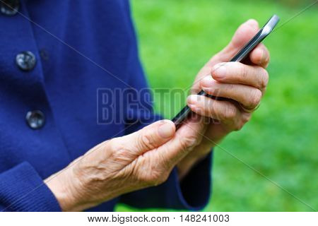 Close-up picture of an old woman holding a cellphone in her hands