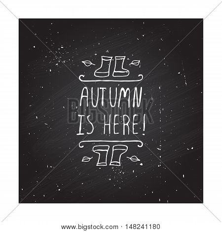 Hand-sketched typographic element with rubber boots, leaves and text on blackboard background. Autumn is here