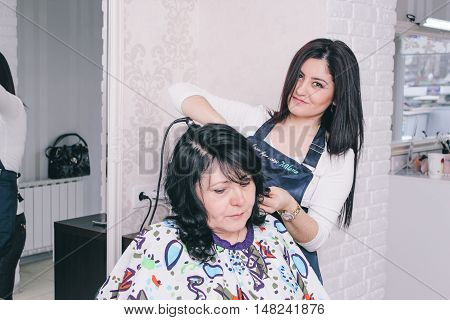 Dneprodzerzhinsk, Ukraine - March 28, 2016: Hairdresser Makes Hairstyle To The Client Of Beauty Salo