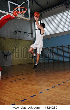 un hombre joven sano jugar juego de baloncesto en el gimnasio de la escuela interior