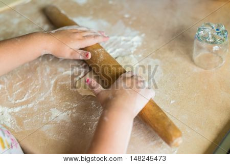 Children's hands holding a rolling pin and roll the dough on the table