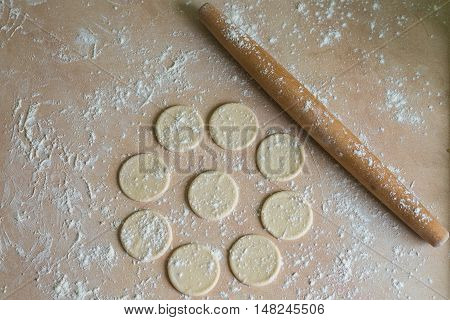 The dough rolled with circles and rolling pin for made ravioli on a wooden table