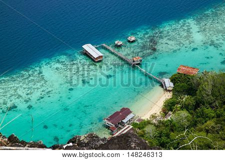 View of jetty at Bohey Dulang,Tun Sakaran Marine Park  island Semporna,Sabah.Mirror smooth ocean surrounded by mountains.The bright blue water and rocky shore in the tropical island of Semporna,Borneo