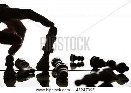 Hand tilting the figure of the king on the chessboard.Focus on the figure of King.Soft focus
