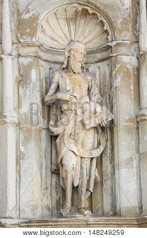 COIMBRA PORTUGAL - AUGUST 1 2016: Statue of Saint John the Baptist in a niche of the front facade of the Old Cathedral in Coimbra Portugal