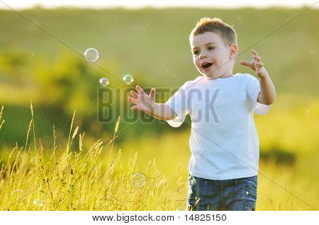 happy young beautiful child have fun on eadow with soap bubbles toy