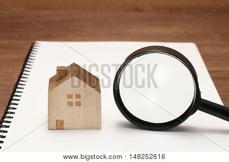 Miniature house, magnifying glass, and notebook. New house concept.