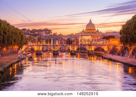 Skyline of Rome in a magenta twilight with San Pietro basilica at Sant'Angelo bridge and Tevere river illuminated by city lights of Roma in Italy