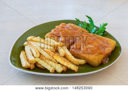 Fish and chips and tomato sauce on the table. Dinner dish.