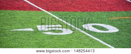 The 50-yard-line of an american football field with artificial turf