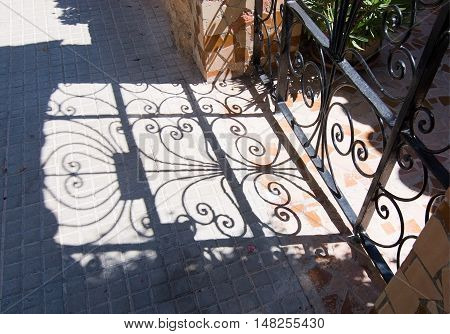 CALA FORNELLS MALLORCA SPAIN - SEPTEMBER 6 2016: Beautiful shadow play from wrought iron fence on a sunny day on September 6 2016 in Cala Fornells Mallorca Spain.