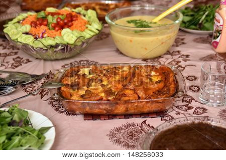 Iranian cuisine with lasagna and salad in the sofreh