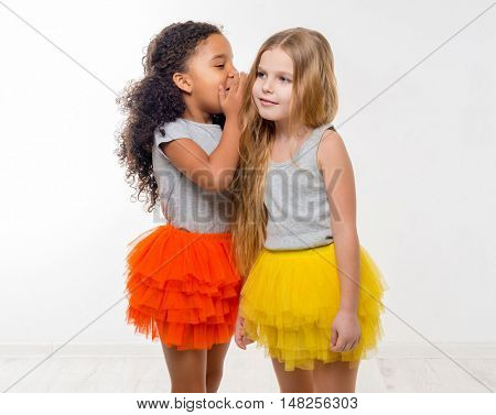 two little smiling girls with different complexion gossiping isolated on white background