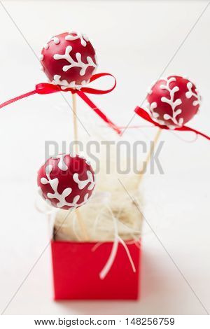 Red cake pops garnished with white icing sticking in red gift box. Very shallow depth of field