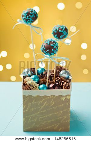 Chocolate cake pops garnished with turquoise icing sticking in nice Christmas gift box. Very shallow depth of field with Christmas lights in the background