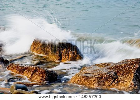 cool waves hit the cliff with spray of water