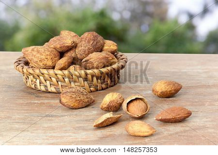 Almonds are roasted on wooden nature background