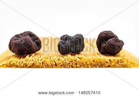 Three mushroom truffle which lie on the pasta spaghetti white background