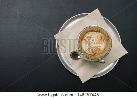 hot fresh coffee in see through glass with silver spoon on black table at coffee time topview / hot fresh coffee