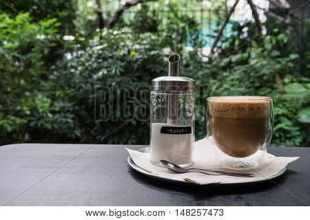 hot fresh coffee in see through glass with sugar in jar; silver spoon on black table at coffee time / hot fresh coffee